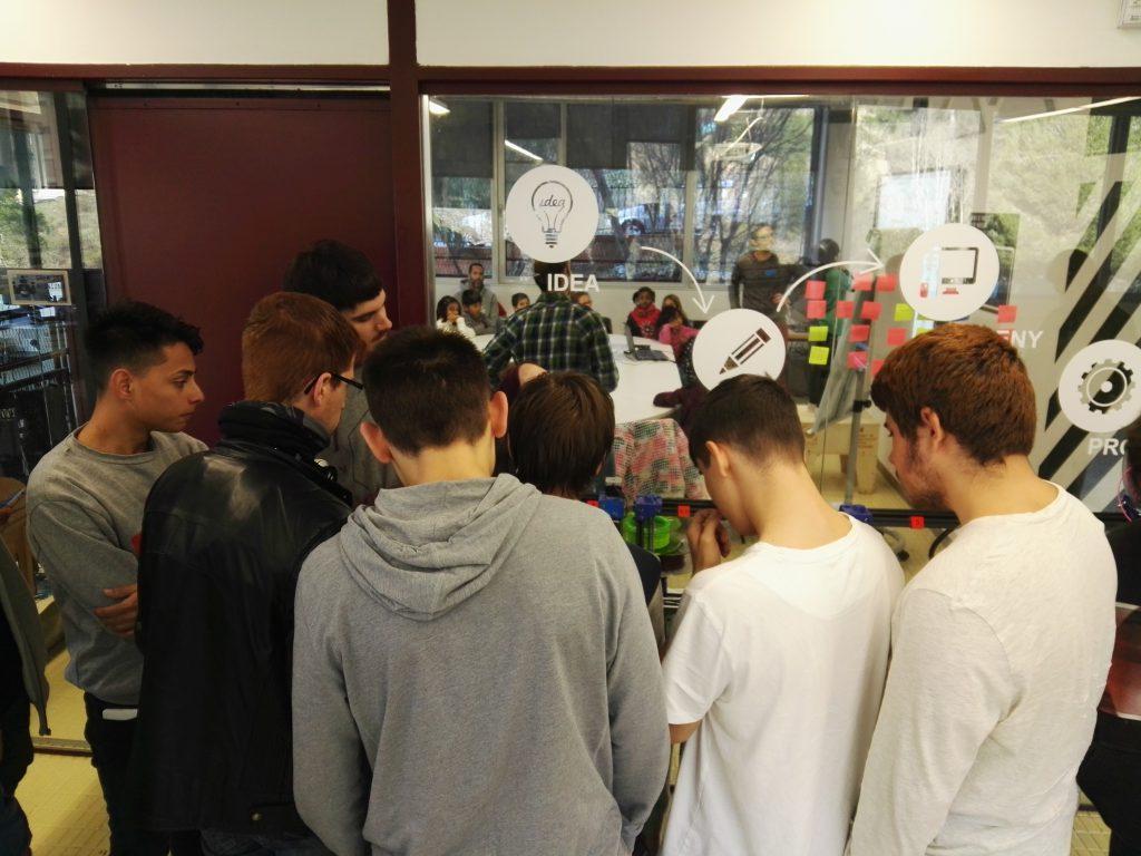 Jóvenes participantes en la formación de YAMakers observando una impresora 3D.