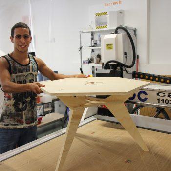 Ibrahim mostrando una mesa fabricada con la fresadora